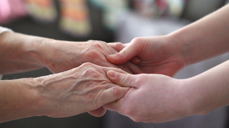 Eine alte Frau hält die Hände einer jungen Frau