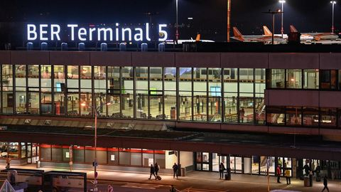 """Der neue Schriftzug """"BER Terminal 5""""leuchtet am Abend auf dem Dach vom ehemaligen Flughafens Berlin Schönefeld"""