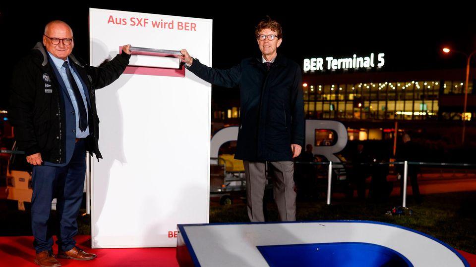 """Am 25. Oktober: Der Bürgermeister von Berlin-Schönefeld, Christian Hentschel (li), und Engelbert Lütke Daldrup (re), Vorsitzender der Geschäftsführung der Flughafen Berlin Brandenburg, bei der Umbenennung des ehemaligen Flughafens Berlin-Schönefeld in """"BER Terminal 5""""."""