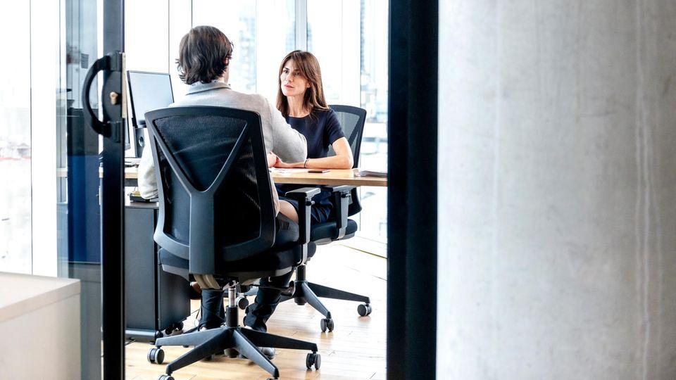 Ein Mann und eine Frau sitzen in einem Büro und unterhalten sich