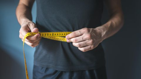Ein Mann hält ein Maßband um seinen Bauch