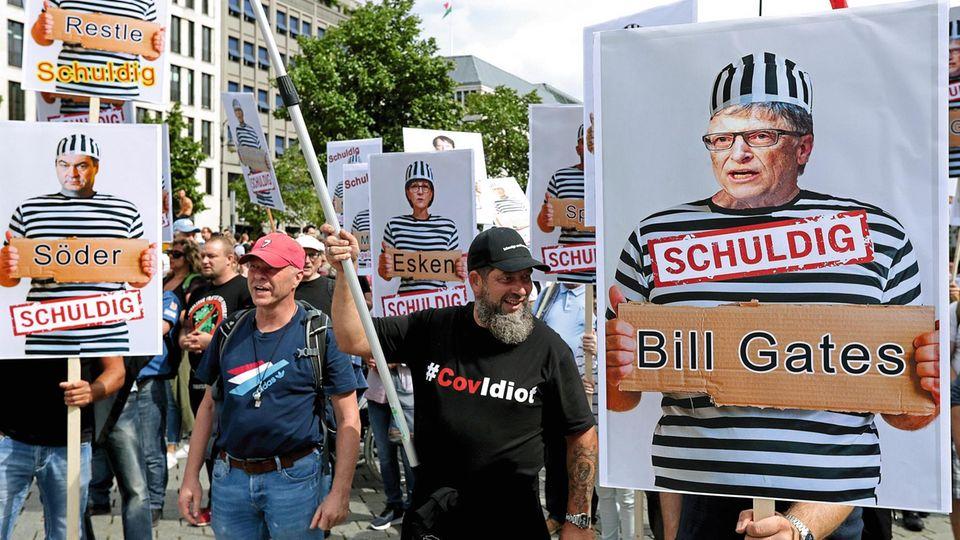 Demonstranten demonstrieren gegen Corona-Richtlinien mit Plakaten