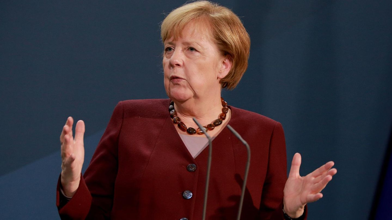 Kanzlerin Angela Merkel spricht mit ausgebreiteten Armen