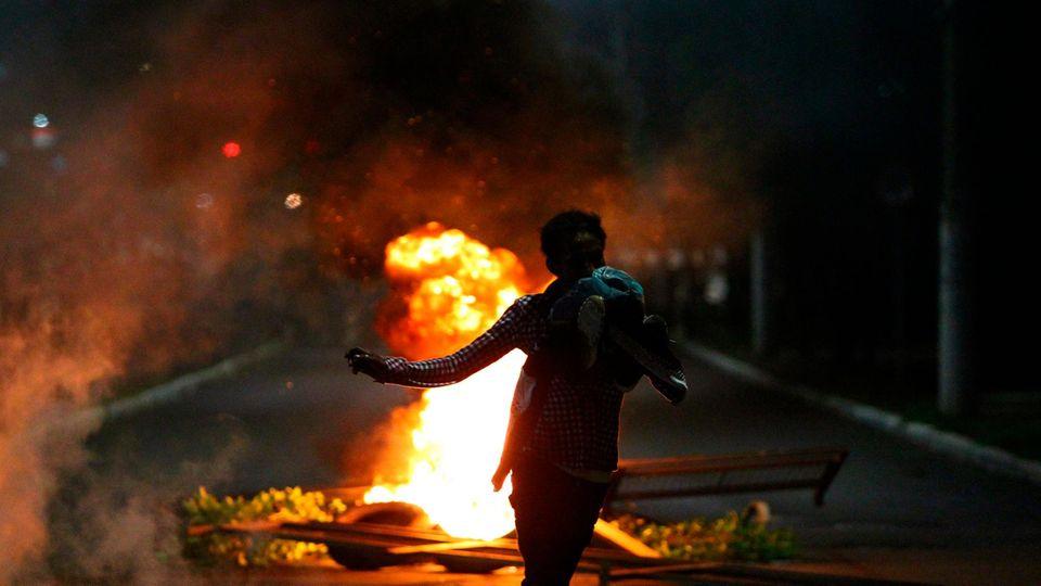Porto Alegre, Brasilien. Ein Demonstrant rennt während eines Protests gegen den Tod von Joao Alberto Silveira Freitas vor der Bereitschaftspolizei weg. Der Tod des Schwarzen, der am Donnerstagabend in einem Supermarkt des Carrefour-Konzerns in Porto Alegre von weißen Sicherheitsbeamten geschlagen wurde, löste in Brasilien eine Welle der Entrüstung aus.