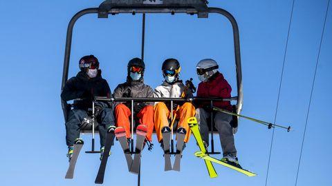 Skifahrer mit Gesichtsmasken fahren im Sesselliftdes Skigebiets Verbier in den Schweizer Alpen.