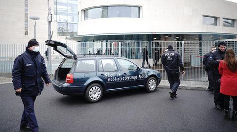 """Ein Auto steht vor dem Tor des Bundeskanzleramts. Auf der Tür ist die Aufschrift: """"Stop der Globailierungs-Politik"""" zu lesen"""