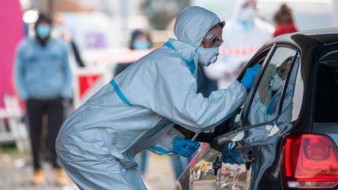 In einen Ganzkörper-Schutzanzug gekleidet ist ein Mitarbeiter eines Corona-Testzentrums auf dem Messegelände in Marburg.