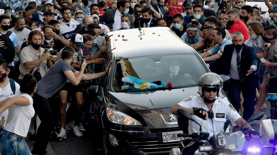 Buenos Aires, Argentinien. Fans der Fußballlegende Diego Armando Maradona bedrängen denLeichenwagen, der den Körper des Toten vom Präsidentenpalast Casa Rosada zum Jardin-de-Paz-Friedhofbringt, woauch seine Eltern begraben wurden.Maradona waram Mittwoch im Alter von 60 Jahren an einem Herzinfarkt gestorben und anschließend im Palast aufgebahrt worden.