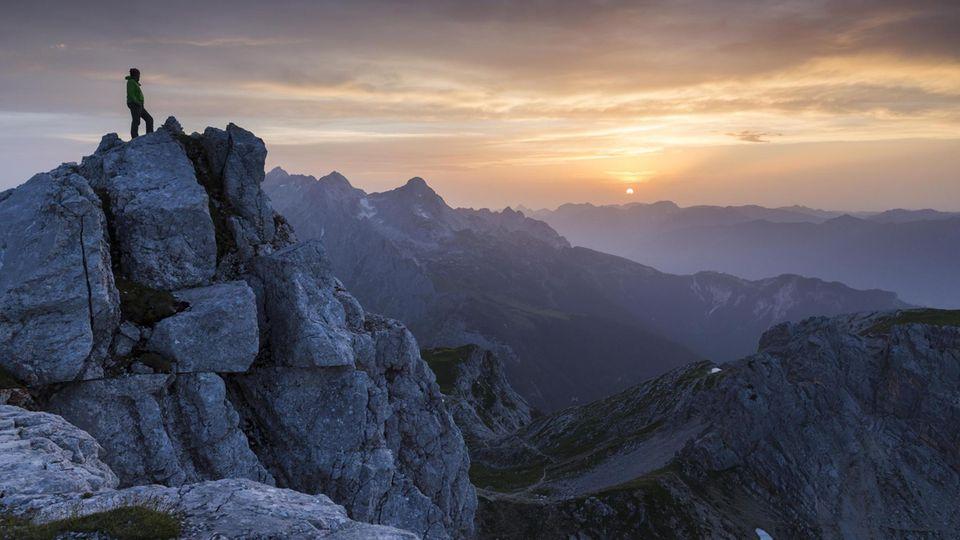 Person steht auf Berg uns schaut in den Himmel