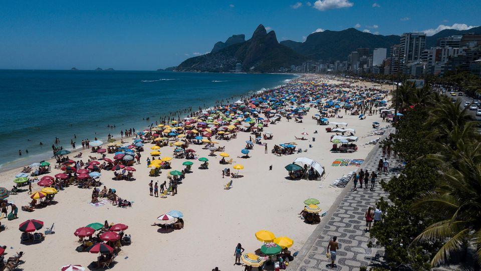 Rio de Janeiro, Brasilien. Tja, Brasilianer müsste man sein. Während bei uns die grauen Wolken tief hängen und die Temperatur sich dem Gefrierpunkt annähert, lassen es sich die Menschen am berühmten Strand von Ipanemabei Mitte 20 Grad gut gehen. Ob das vernünftig ist in Zeiten,in denen die Corona-Infektionen in dem Land in die Höhe schnellen, ist eine andere Frage.
