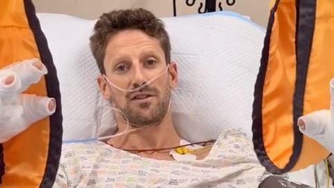 Ein junger Mann mit blondem Seitenscheitel liegt mit beiden Händen in Schlaufen in einem Krankenhausbett