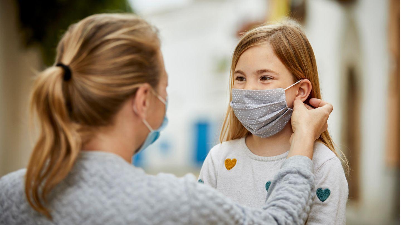 Kinder und Corona: Eine Frau setzt einem Kind einen Mund-Nasen-Schutz auf