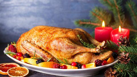 Ganze gebratene Ente mit Orangen, Beeren und Kräutern und Weihnachtsdekorationen
