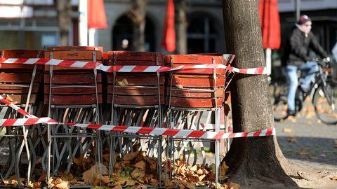 Ein Radfahrer fährt an zusammengestellten Stühlen von Gastronomiebetrieben vorbei