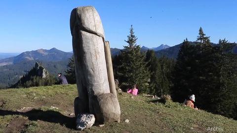 Auf einer Bergkuppe steht ein verwitterter, erigierter Penis aus Holz. Dahinter rasten Wanderer und genießen den Ausblick
