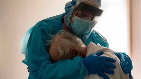 Arzt im Schutzanzug umarmt Patienten