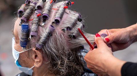 Einer Kundin werden in einem Friseursalon die Haare frisiert