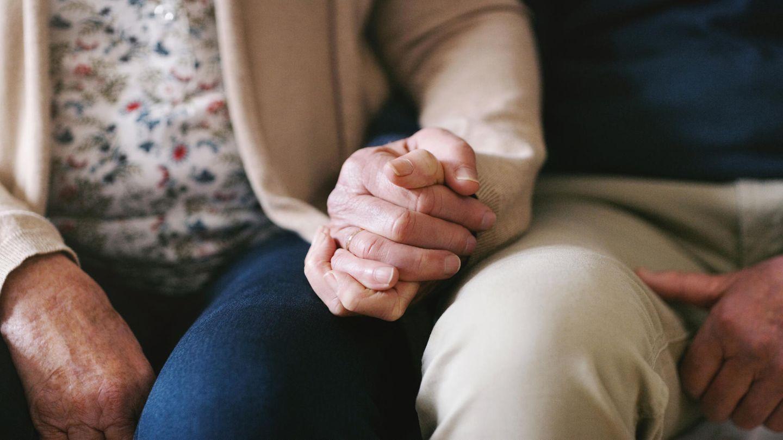 Altes Ehepaar hält sich an den Händen