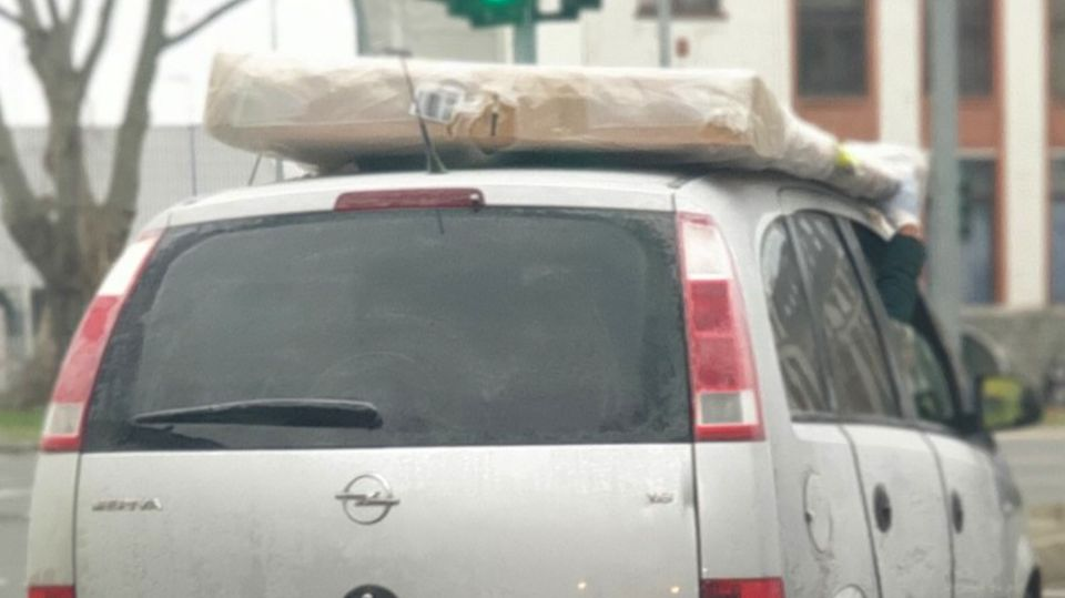 Ein Beifahrer hält eine Matratze auf einem Autodach fest.