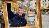 """Micha und Ines Sydow posieren mit Bilderrahmen am Franz-Naumann-Platz. Gleich nebenan, in der Residenzstraße 109 befindet sich die Eventgaststätte """"Kastanienwäldchen"""" von Norbert Raeder. Der sozial engagierte Gastronom nimmt dort werktags ab 16 Uhr Kleiderspenden für Bedürftige entgegen"""