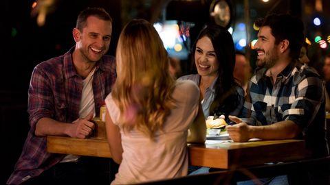 Vier junge Menschen unterhalten sich in einer Bar