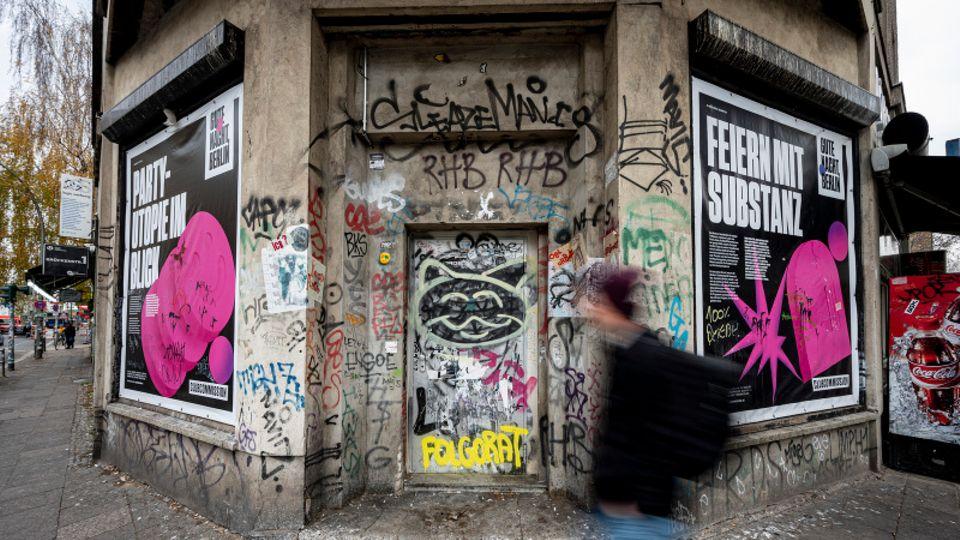 Eine braune Häuserecke in Berlin, darauf sind Poster über das Feiern. Ein Mann läuft auf dem Bild vorbei.