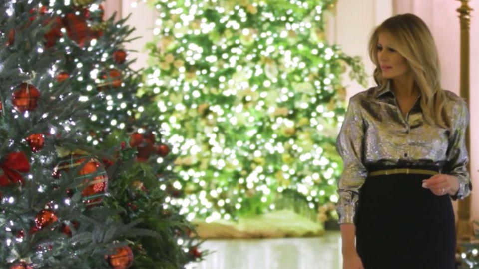 Melania Trump geht durchs Weiße Haus und blickt über die rechte Schulter auf eine Weihnachtsbau mit roten Kugeln