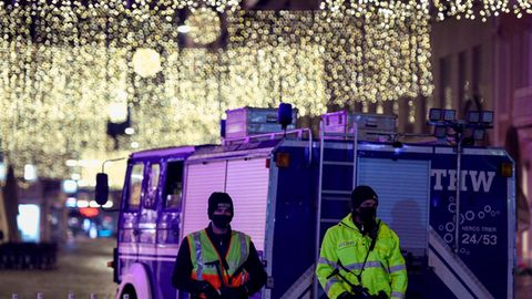 Zwei Polizisten und THW-Lkw vor der weihnachtlich geschmückten Altstadt von Trier