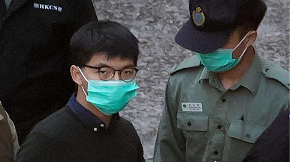 Ein Asiate mit hellgrünem Mundschutz und rundlicher Brille steht neben einem uniformierten Wachmann