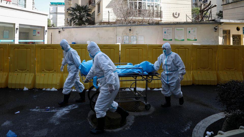 China, Wuhan: Medizinische Mitarbeiter schieben eine Leiche