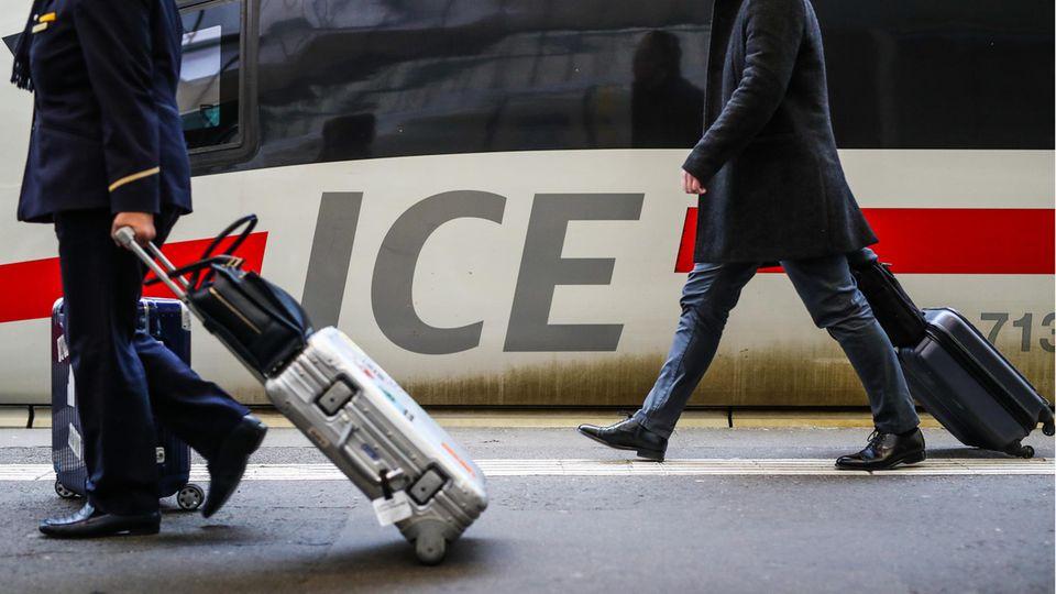 An einer Lok mit ICE-Schriftzug ziehen zwei Fahrgäste ihre Rollkoffer vorbei