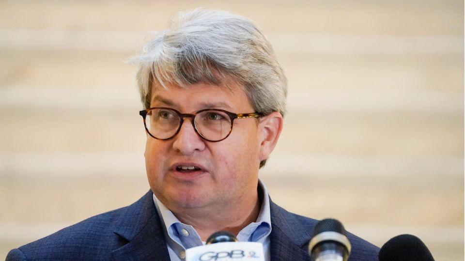 Ein grauhaariger Mann mit Hornbrille und Anzug steht an einem Rednerpult und spricht in Mikrofone