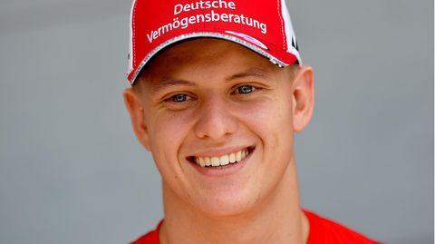 Ein junger Mann in rotem T-Shirt und mit rotem Cap lächelt breit.