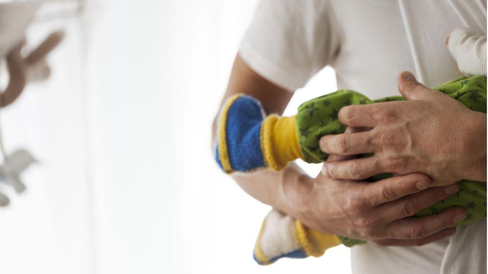 Junger Mann hält Neugeborenes mit Hose und Schühchen im Arm