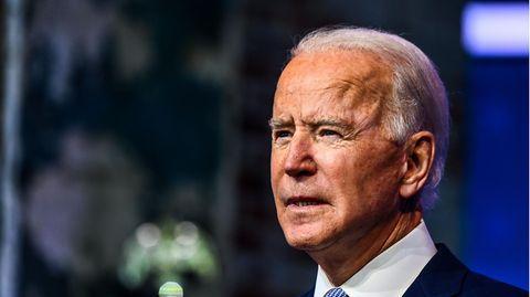 Joe Biden - ein älterer Mann mit weißen, zurückgekämmten Haaren – steht im blauen Anzug vor einem verschwommenen Hintergrund