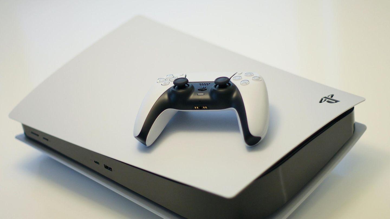 Eine Playstation 5 mit einem Controller liegt auf einem Tisch