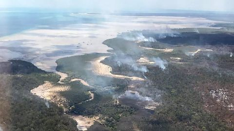 Eine Luftaufnahme zeigt große Flammen und viel Rauch über einer bewaldeten Insel