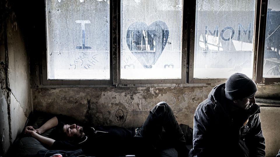 Sayeed (l.) kommt aus Afghanistan. An das einzig verbliebene Fenster in der verfallenen Metallfabrik von Bihac hat er einen Gruß an seine Mutter geschrieben. Wenn sie telefonieren sagt er ihr, dass alles gut sei
