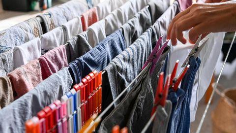 Eine Frau hängt frisch gewaschene Textilien auf einen Wäscheständer