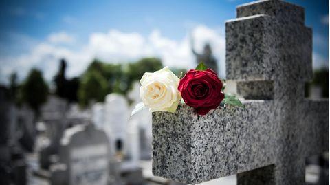 Friedhofskreuz mit einer weißen und einer roten Rose darauf