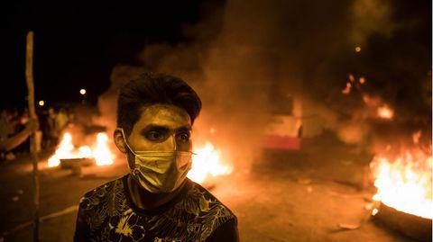 Ein Mann mit Mundschutz steht vor brennenden Barrikaden