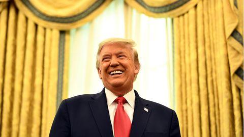Vor einem Fenster mit schweren goldenen Vorhängen steht US-Präsident Donald Trump und lacht