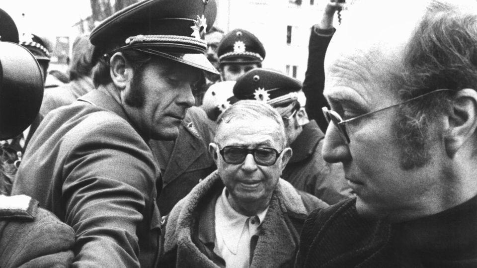 4. Dezember 1974: Sartrebesucht Baader in der Haft  Polizeibeamte bahnen am 4. Dezember 1974 Jean-Paul Sartre (M.) den Weg bei seiner Ankunft vor dem Stammheimer Untersuchungsgefängnis. Der Philosoph hatte zuvor vor dem Oberlandesgericht Stuttgart die Erlaubnis erstritten, den RAF-Terroristen Andreas Baader in der Haft zu besuchen. Baader-Anwalt Klaus Croissant hatte das Treffen eingefädelt, um der Ideologie der Roten Armee Fraktion in der Öffentlichkeit Sympathien zu verschaffen und um Kritik an den Haftbedingungen der Terroristen Nachdruck zu verleihen. Doch Sartre und Baader sollen sich in dem gut einstündigen Gespräch nicht gerade sympathisch gewesen sein. Zudem mussten sie den Dialog per Übersetzer führen – der Franzose sprach kein Deutsch, Baader kein Französisch. Sartre äußerte nach dem Treffen in einer Pressekonferenz allerdings Kritik an den Haftbedingungen der RAF-Terroristen.