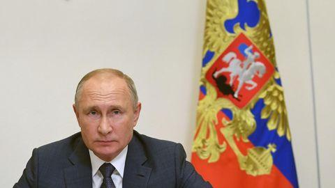 Russlands Präsident Wladimir Putin sitzt im Anzug an seinem Schreibtisch. Hinter ihm Russland-Flaggen und -Wappen