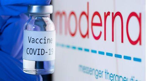Ampulle Corona-Impfstoff von Moderna vor dem Firmenlogo