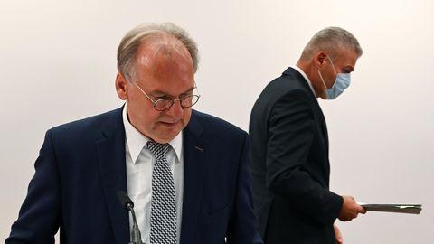 Ein Mann mit Brille und Halbglatze steht im Anzug im Vordergrund, während hinter ihm ein anderer Mann seitlich weggeht