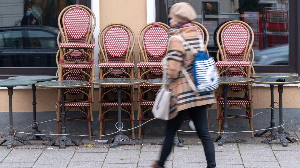 Eine Frau geht an einem geschlossenem Cafe vorbei
