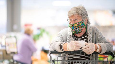 Eine ältere Frau mit kurzen, weißen Haaren trägt eine Maske und schiebt einen Einkaufswagen zwischen Supermarkt-Regalen