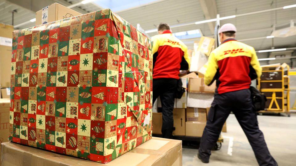 Ein großes Paket in Weihnachtspapier liegt auf einem Stapel Kartons, während im Hintergrund DHL-Mitarbeiter