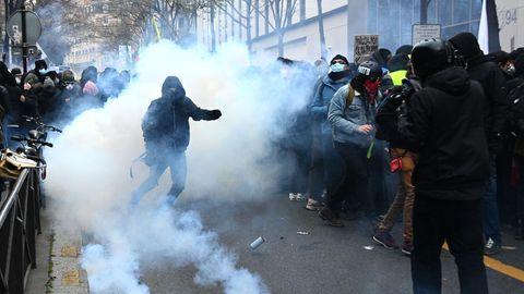 Ein schwarz vermummter Demonstrant steht in einer Tränengas-Wolke auf einer Straße in Paris